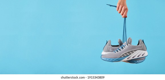 Hand holds hanging gray running sneakers by the laces on blue pastel background.  Hand with a new sport shoe. Stability and cushion running shoes. Close up.