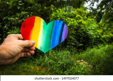 Hand holds a heart painted rainbow colorful garden background. Equality between homosexuals and heterosexuals concept.  LGBT community. (lesbian , gay , bisexual ,transgender ,transsexual)