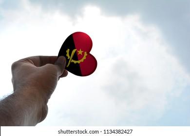 Hand holds a heart Shape Angola flag