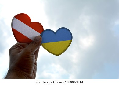 Hand holds a heart Shape Austria and Ukraine flag, love between two countries