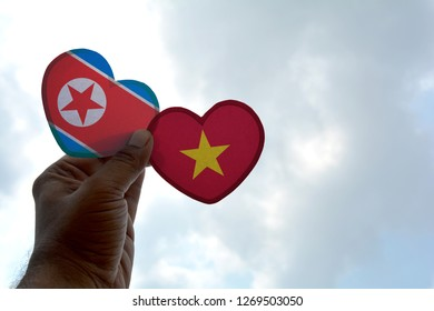Hand holds a heart Shape North Korea and Vietnam flag, love between two countries