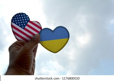 Hand holds a heart Shape USA and Ukraine flag, love between two countries