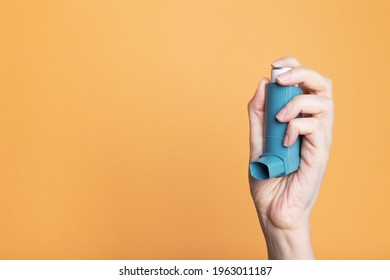 Hand holds inhaler to treat asthma. World Asthma Day. Concept of allergy care. Copy space