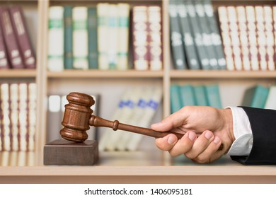 Hand holds justice gavel on library background