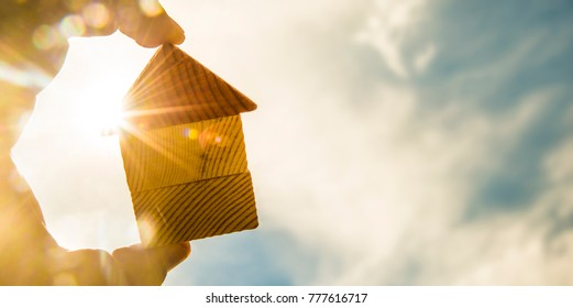 hand holds the last pieces of wooden house puzzle on blue sunny sky background. wooden home made from natural material of jigsaw. puzzle in the form of wood house. for sale or rent