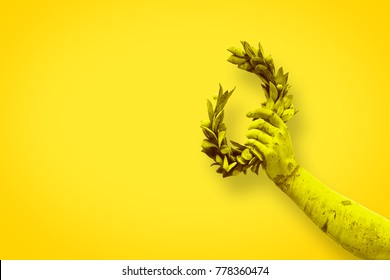 Hand holds a laurel wreath - bronze statue on solid color background - Success and fame concept image with copy space