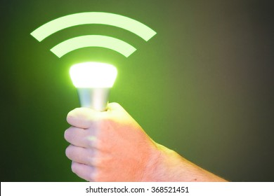 Hand holds a Lifi symbol with glowing bulb combined with wifi symbol