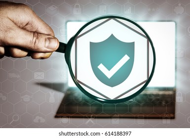 Hand holds the magnifying glass in front of an open notebook. Among the many icons, attention is focused on the shield icon. Antivirus, hacker protection.