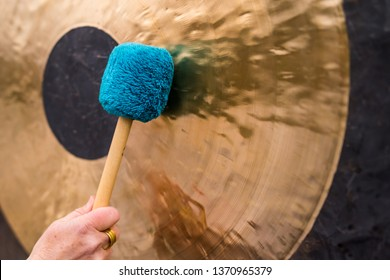 Hand holds a mallet and beats a gong