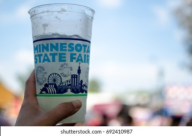 A hand holds up a Minnesota State Fair cup with a blurred background. The Minnesota State Fair runs for 12 days near the end of summer.