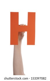 A Hand Holds an Orange H, Isolated