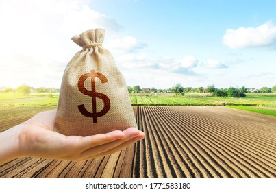 A hand holds out a dollar money bag on a background of a farm field. Lending farmers and agricultural enterprises for purchase land and seed material, equipment modernization Support and subsidies.