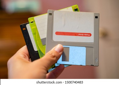 Hand holds out Three outdated 3.5 inch floppy disks, from the 1990s