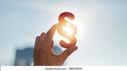 Hand holds paragraph symbol in the sun in the sky