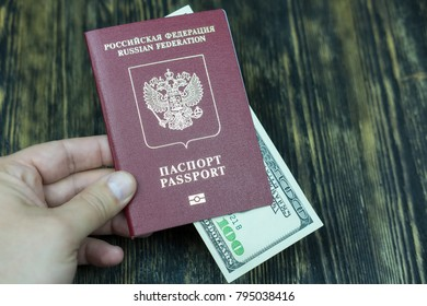 Hand holds a passport with money