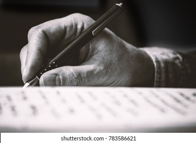A hand holds a pen and writes into a book