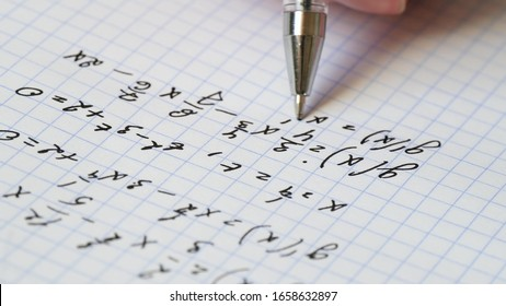 The hand holds a pen and writes a mathematical formula in a notebook. Solution of equation. The concept of education and research.