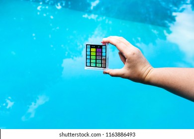 hand holds pH meter for measure the acidity of water in a swimming pool