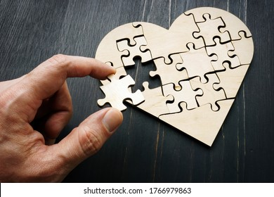 The hand holds a piece of the puzzle in the form of a heart.