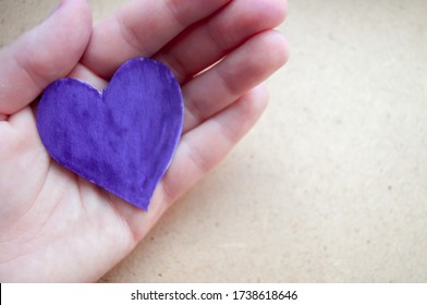 Hand holds a purple heart. Expression of understanding and compassionate love. Love and caring. The concept of parents and children. Military medal for wounded soldiers.