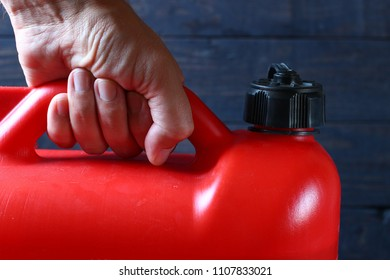 The hand holds a red canister