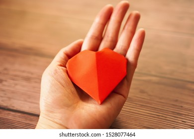 A hand holds an red origami paper heart on wooden background show concept of Donate,Give, Love ,Valentine ,Sweetest day concept