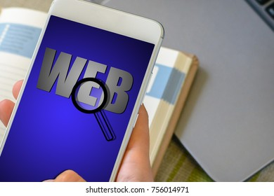Hand holds a smartphone with text web and loupe on phone screen  over a notebook and a laptop