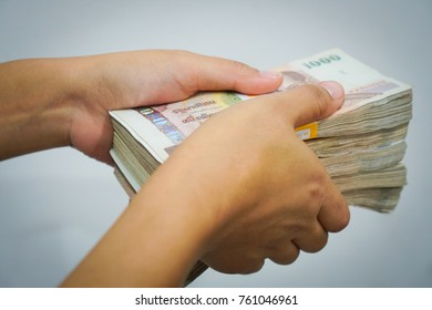 Hand holds Thailand money on brown background, close up