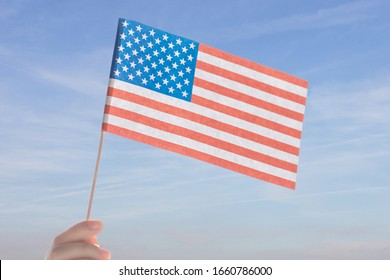 Hand holds USA flag on sky background