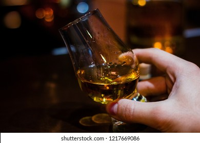 hand holds whiskey in a special glass for tasting with space for text