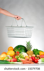 A hand holds a wire shopping basket over a selection of fresh produce.