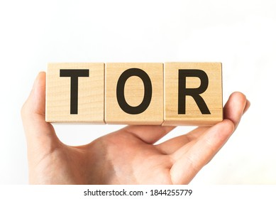 Hand holds wooden cubes with letters tor. Business concept image.