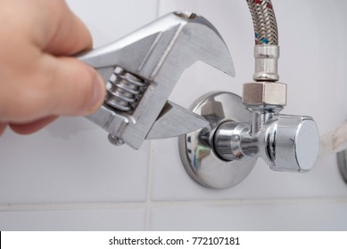 hand holds a wrench near the faucet and hoses