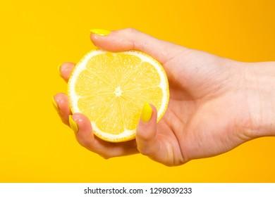 Hand holds yellow lemon in front of lemon background