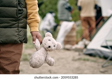 Hand of homeless child holding white teddybear while standing against refugee camp