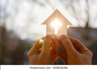 Hand with a house from paper and a cross on a background of sunrise.