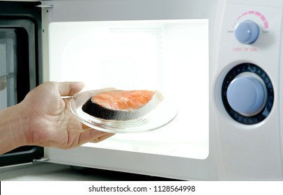 Hand of housewife are cooking steak fish with microwave oven for dinner with her family. She prepared by putting fish dish into microwave oven and then she serve health food. Cooking food concept.