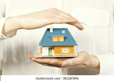 hand hovering small family house, home insurance concept