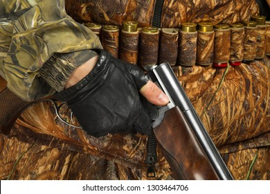 the hand of the hunter in glove holding an unloaded double-barreled shotgun