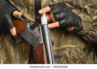 hand of the hunter in gloves puts a cartridge in the shotgun