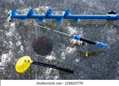 hand ice auger and fishing rod on the ice