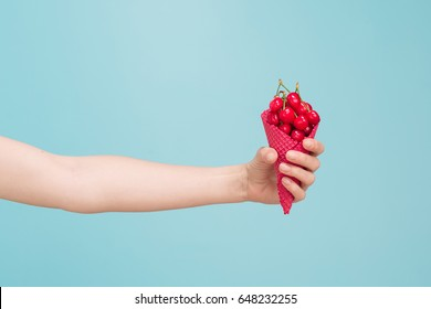 Hand with ice cream waffle cone and cherries