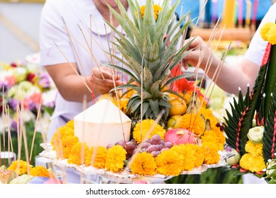 Hand incense stick to fruits and flowers for making offerings or sacrifice to the spirits at construction site.
