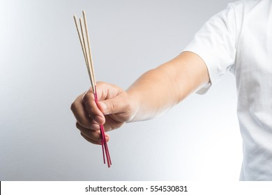 hand with incense stick on white background