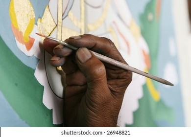 The hand of an Indian artist painting a Hindu God with a squirrel hair brush