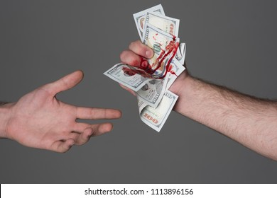Hand injured bloody finger holds dollar banknote grey background. Dirty money concept. Bloody currency. Money covered with traces of crime. Handover criminal profit. Dollar marked by murder.