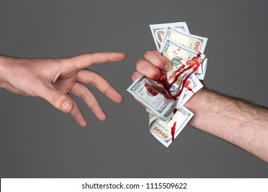 Hand injured bloody finger holds dollar banknote grey background. Dirty money concept. Bloody currency. Handover criminal profit. Dollar marked by murder. Money covered with traces of crime.