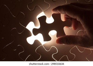 Hand insert jigsaw, conceptual image of business strategy