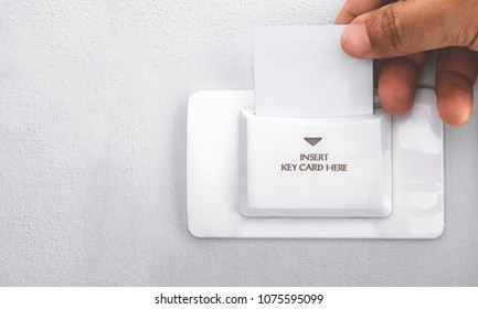hand insert key card in the hotel room
