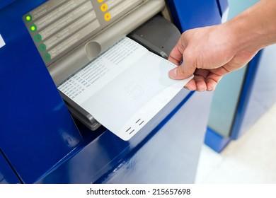 hand inserting account bankbook into automatic passbook update machine